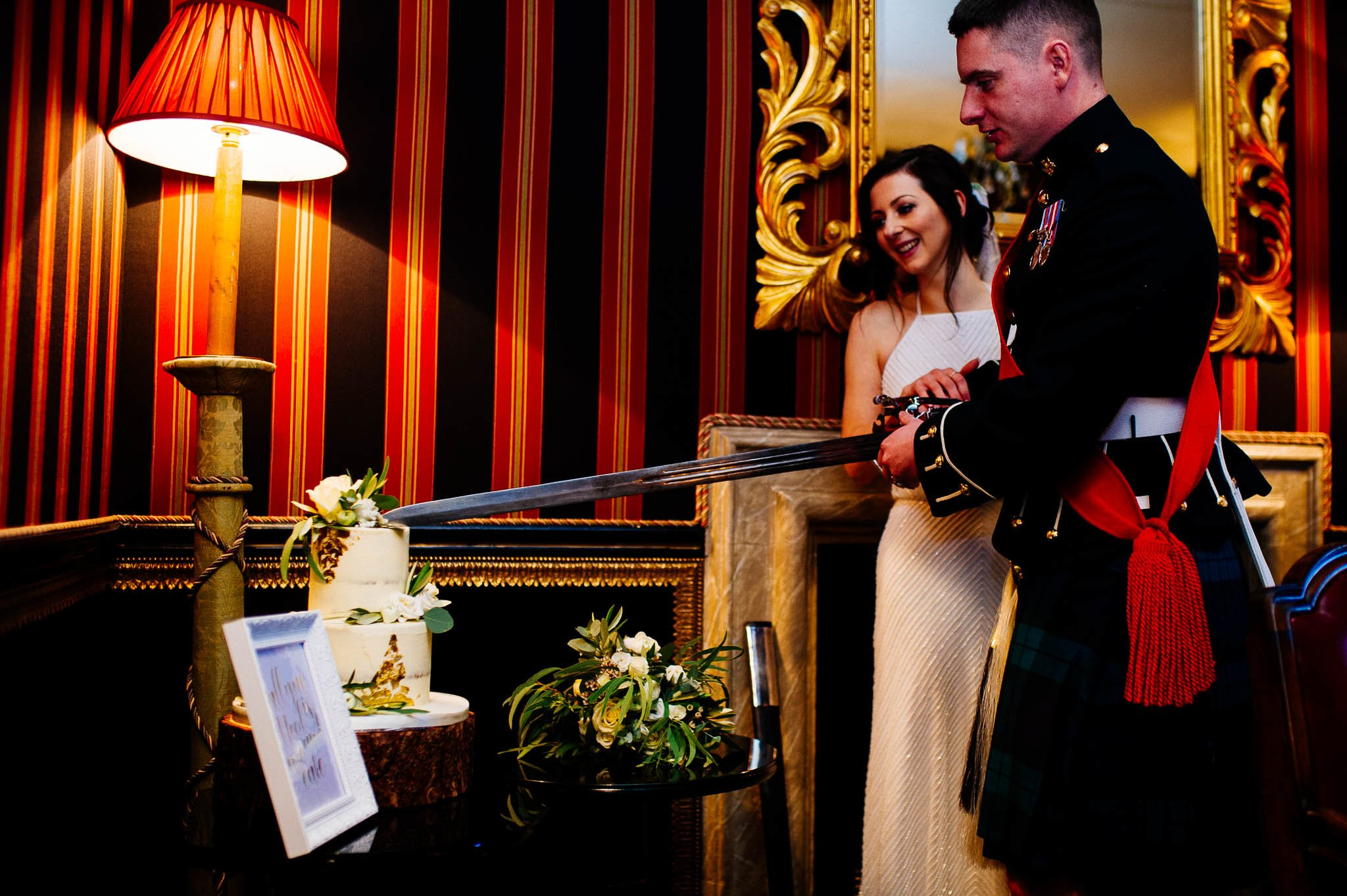 Nowożeńcy kroją tort ślubny szablą