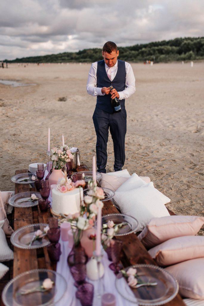 Pan młody otwiera szampana na weselu nad morzem w Gdańsku