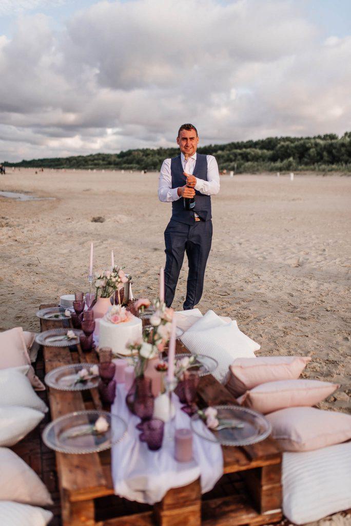 Pan młody ptwiera szampana na plaży w Gdańsku