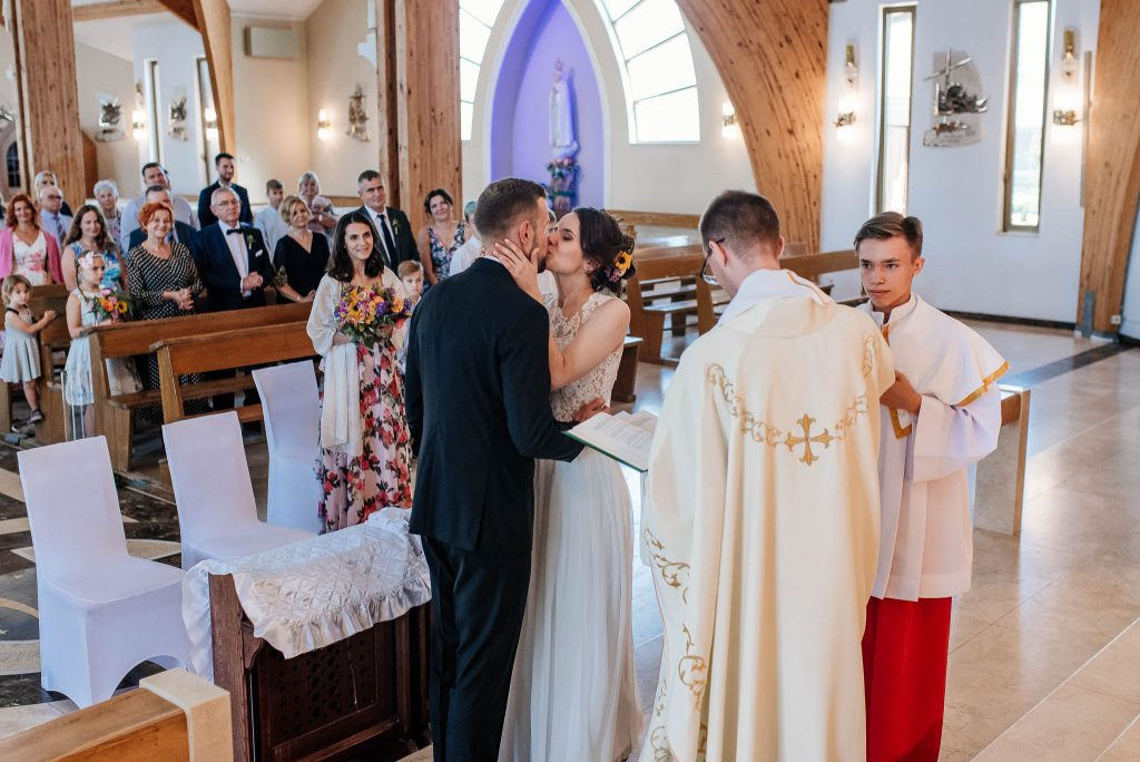 Pocałunek państwa młodych podczas ślubu w parafii św Ojca Pio w Gdańsku