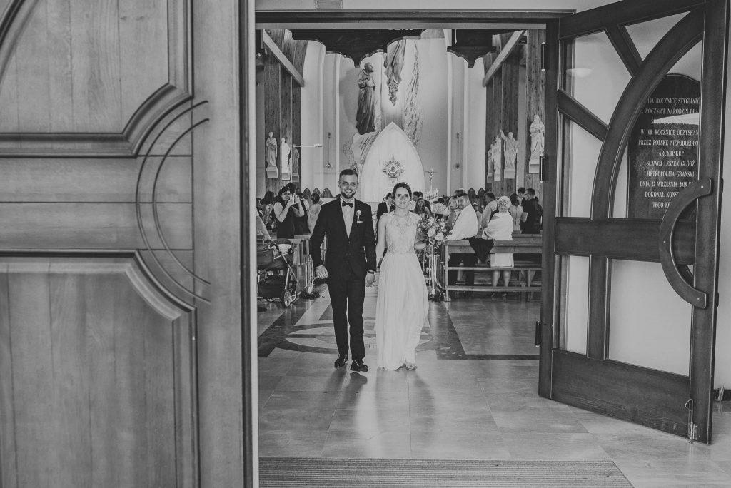 Młodzi wychodzą z kościoła po ślubie