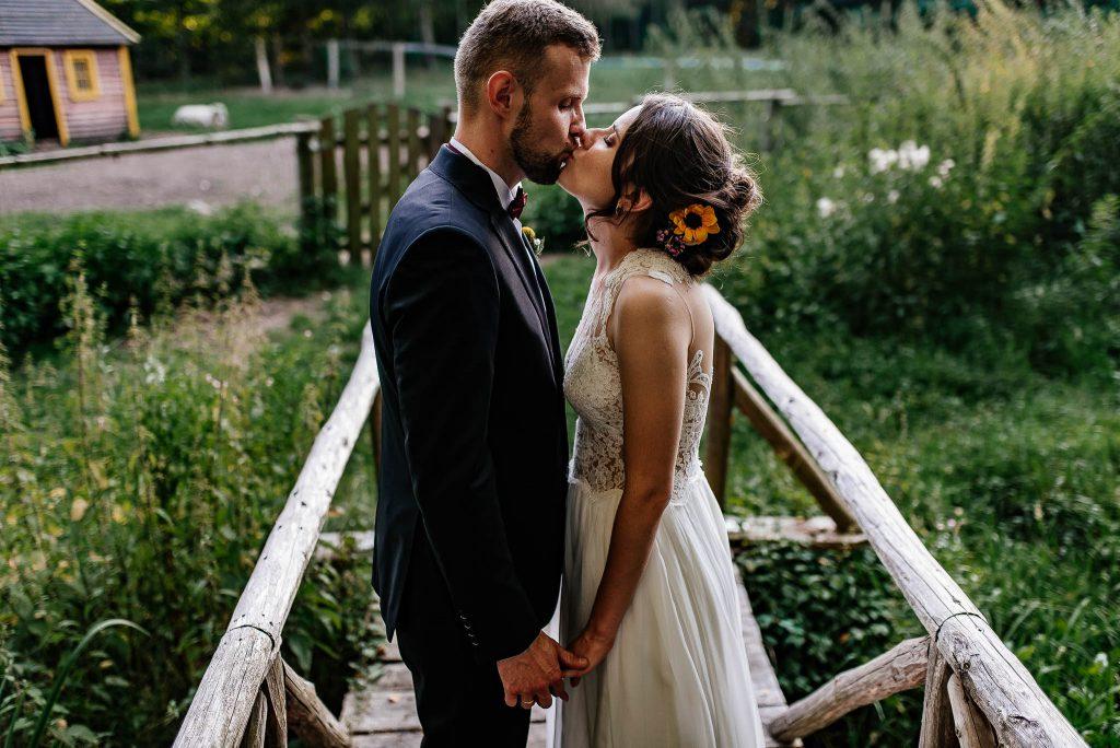 Pocałunek nowożeńców na sesji plenerowej w lesie
