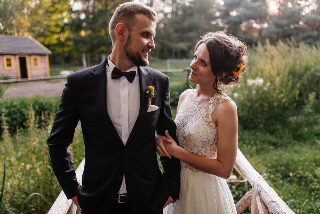 Nowożeńcy spoglądają na siebie na sesji w lesie niedaleko Karczmy Swojak