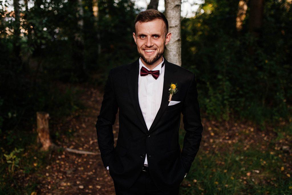 Uśmiechnięty Pan Młody w lesie