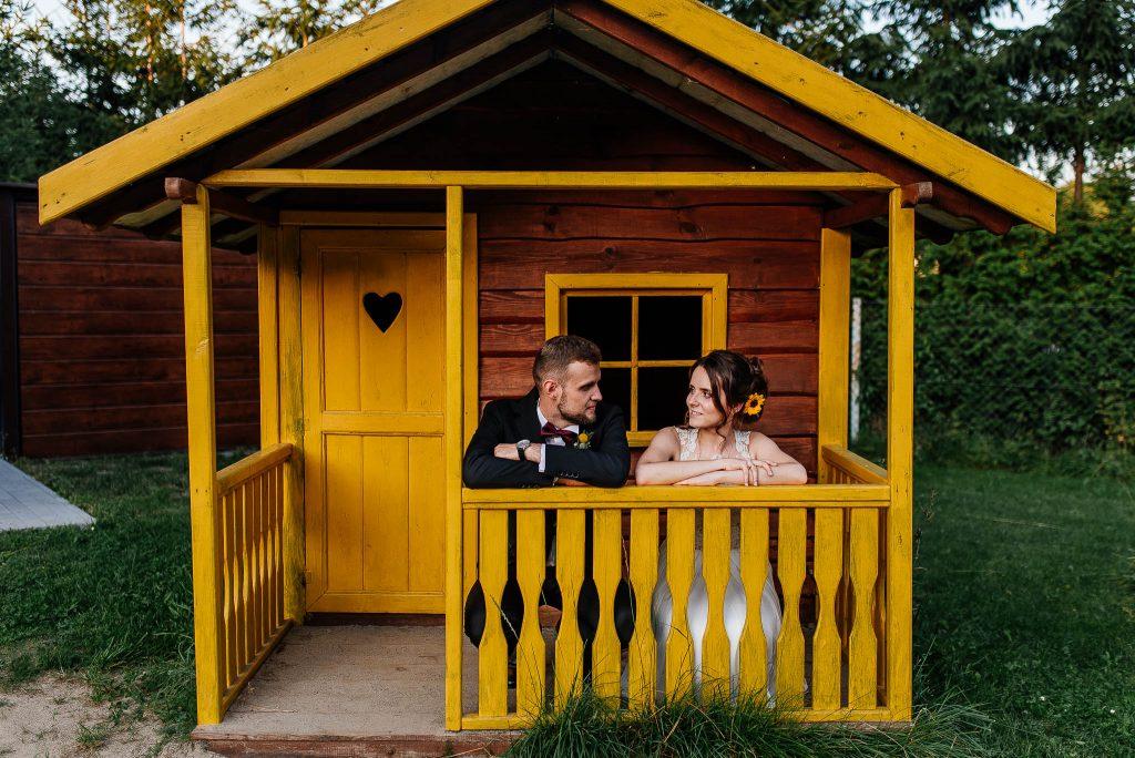 Sesja plenerowa w żółtym drewnianym domku