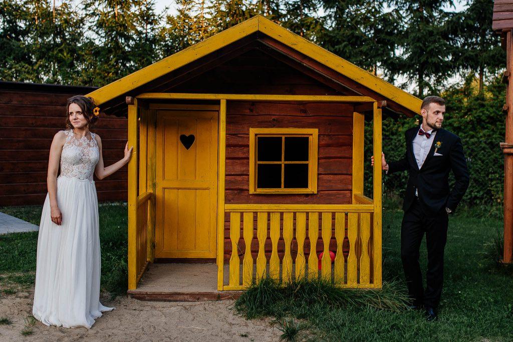 Nowożeńcy na sesji ślubnej przy drewnianym domku
