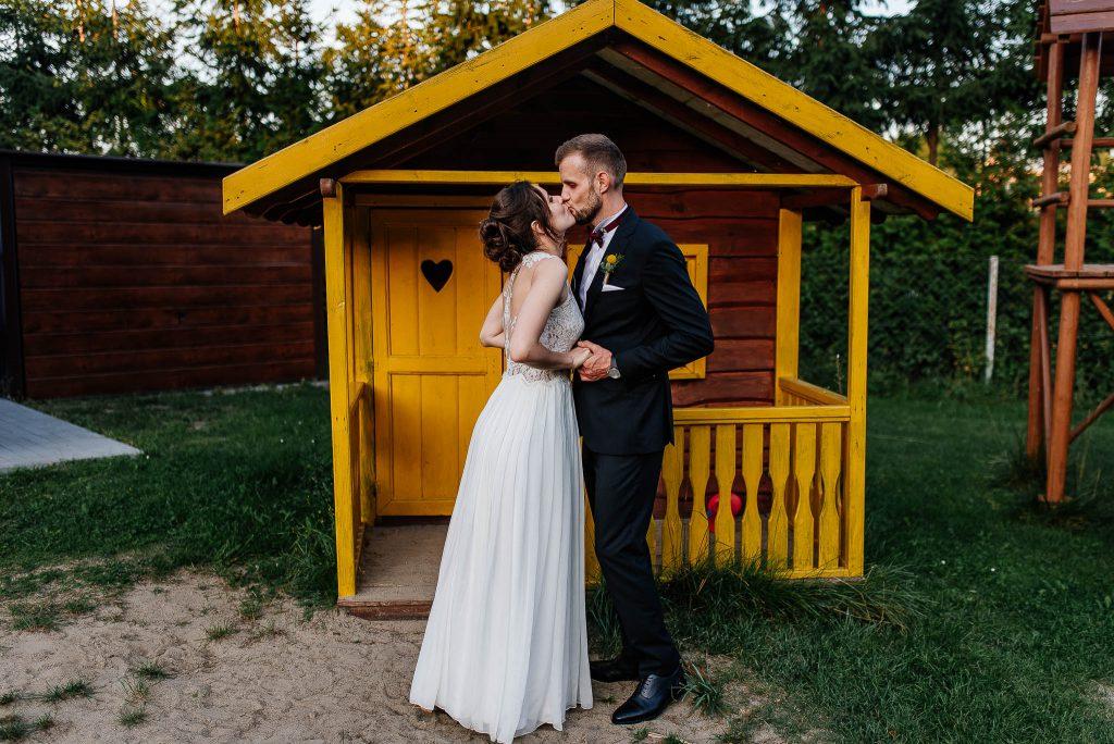 Pocałunek nowożeńców na sesji przy drewnianej szopce podczas wesela w karczmie Swojak w gdańsku