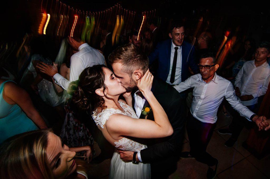 Nowożeńcy całują się na parkiecie podczas zabawy weselnej