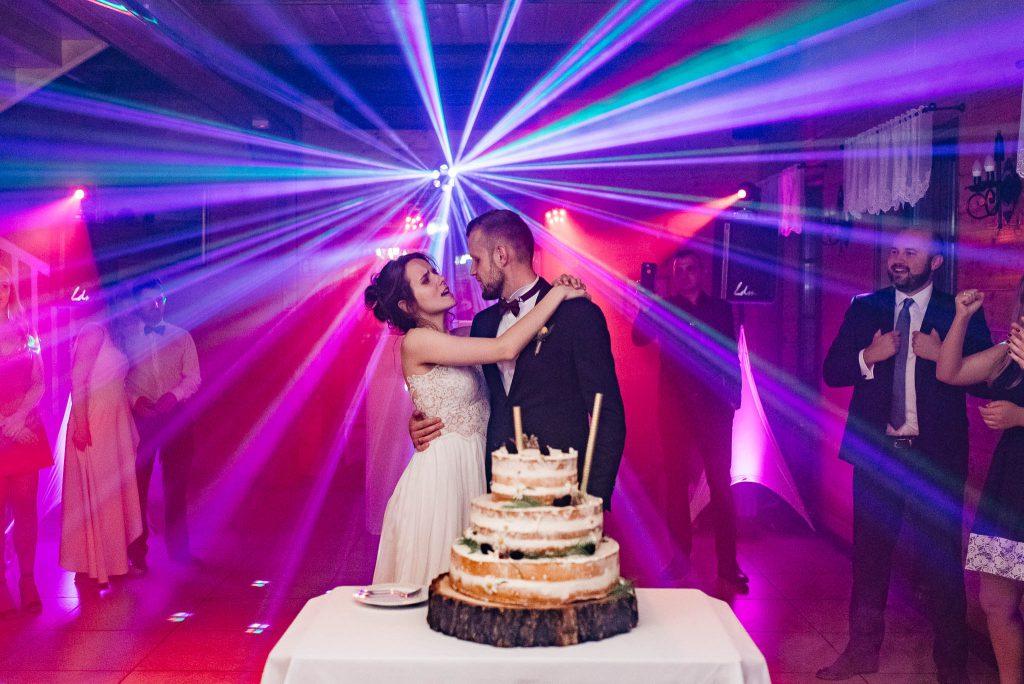 Tort weselny z nowożeńcami w tle