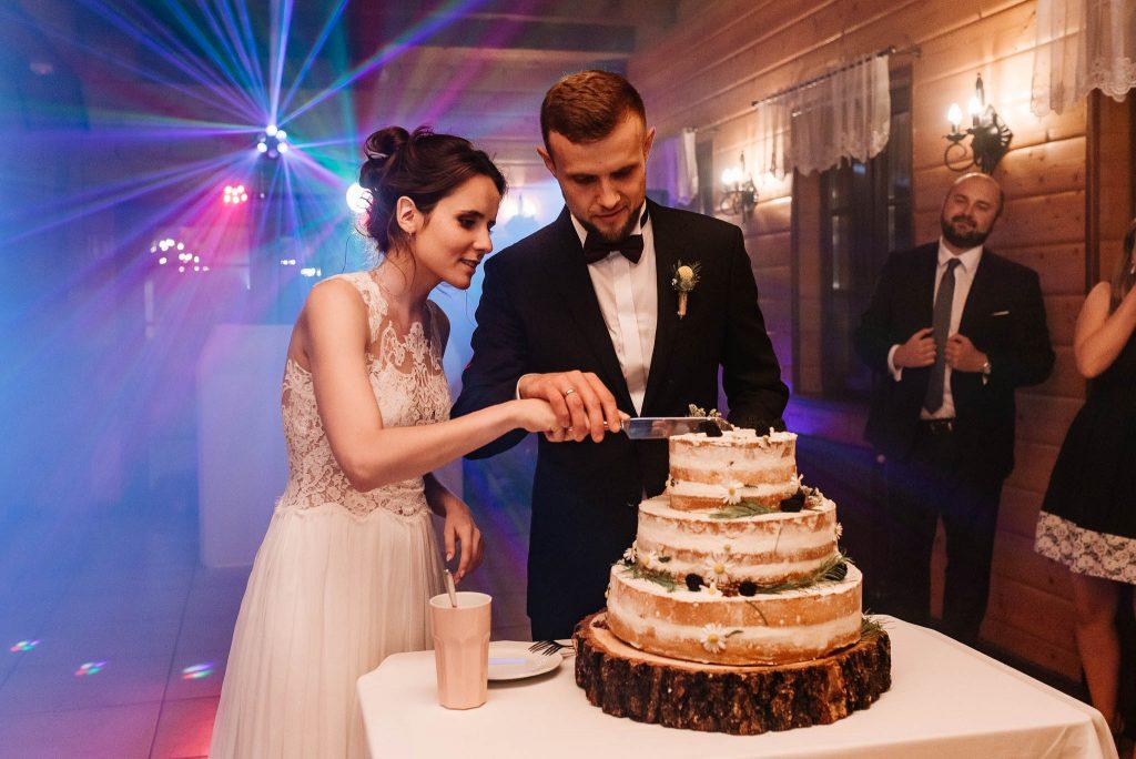 Nowożeńcy kroją tort na zabawie weselnej
