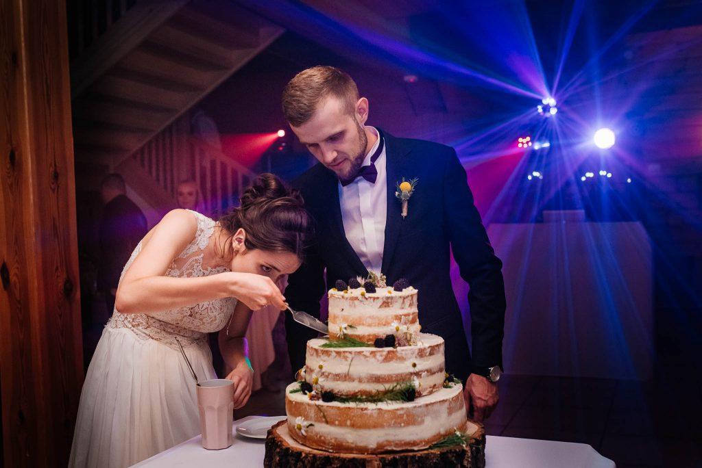 Pani młoda kroi tort na weselu w Gdańsku