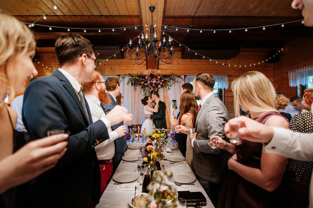 Pocałunek państwa młodych przy stole weselnym Karczma Swojak Otomin