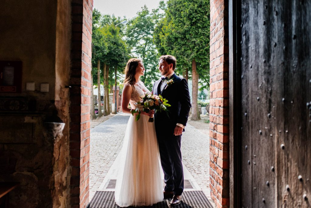 Para Młoda w drzwiach kościoła tuż przed ceremonią ślubną w kościele w Lubiszewie Tczewskim