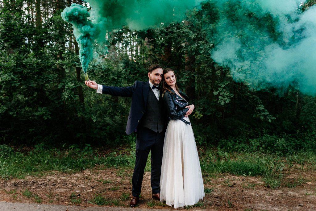 Para Młoda z zielonymi świecami dymnymi w lesie
