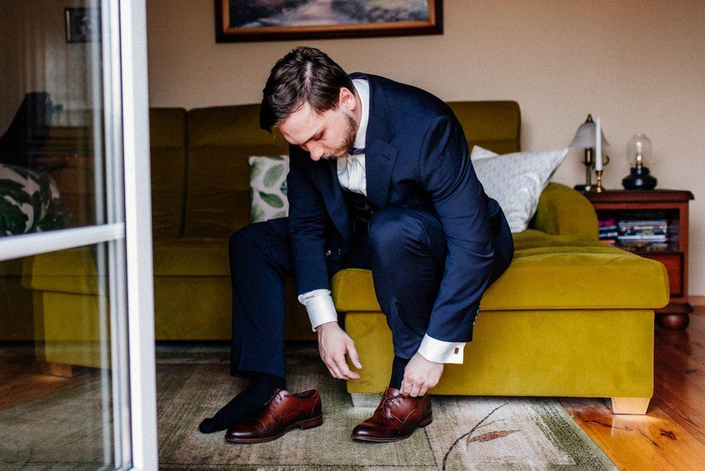 Pan Młody nakłada buty podczas przygotowań